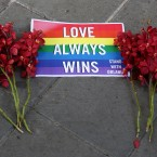 A sign and flowers lie on the ground outside the US Embassy during a vigil for those killed and wounded in the Sunday June 12, 2016 mass shooting at a gay nightclub in Orlando, Florida, in Bangkok, Thailand on Monday.