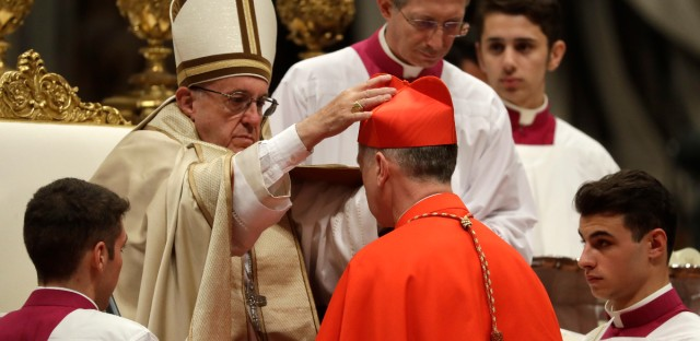 New Cardinal Blase Cupich, Archbishop of Chicago, United States, receives the red three-cornered biretta hat during a consistory inside the St. Peter's Basilica at the Vatican, Saturday, Nov. 19, 2016. In the ceremony to formally give the Catholic church 17 new cardinals, Francis lamented how immigrants, refugees, and those from different races or faiths are increasingly seen as enemies.