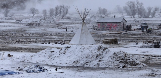 Snow falls on the Oceti Sakowin camp on Monday as structures smolder.