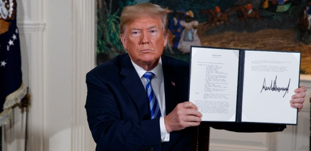 President Donald Trump shows a signed Presidential Memorandum after delivering a statement on the Iran nuclear deal from the Diplomatic Reception Room of the White House, Tuesday, May 8, 2018.