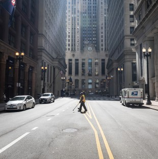 A sanitation worker crosses South LaSalle Street in downtown Chicago.