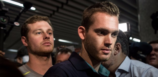 U.S. Olympic swimmers Gunnar Bentz and Jack Conger leave the police headquarters at Rio de Janiero's international airport on Thursday.