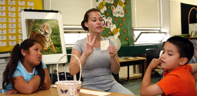 Stephanie Butler, 19, uses flash cards as summer school students Esbeydi Soria Parra, left, and Ramsey Prieto, right, sound out the word at Woods Lake Elementary School Monday, Aug. 6, 2007, in Kalamazoo, Mich. Butler, a junior at Michigan State University this fall was among the first students to benefit from The Kalamazoo Promise, an anonymously funded free-tuition program for graduates of the district's high schools.