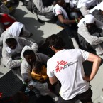 Members of Médecins Sans Frontières (Doctors Without Borders) and SOS Méditerranée distribute food to migrants and refugees aboard the rescue ship Aquarius on May 25, a day after a rescue operation off the Libyan coast.