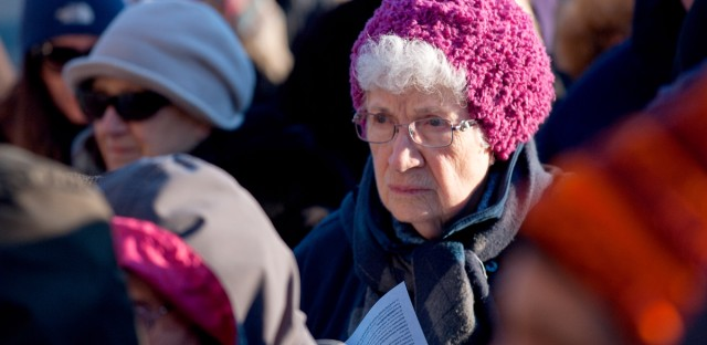 A woman listens in at an interfaith vigil at the ICE Broadview Processing Facility on March 3, 2017. (Bill Healy/WBEZ)