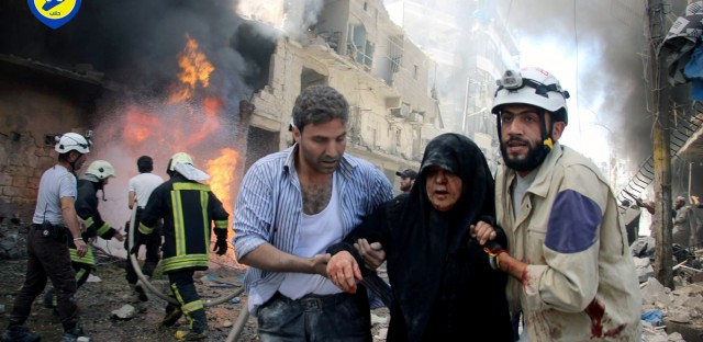 In this file photo taken in June, provided by the Syrian Civil Defense Directorate in Liberated Province of Aleppo, which has been authenticated based on its contents and other AP reporting, shows Syrian civil defense workers help an injured woman after warplanes attacked a street, in Aleppo, Syria. Residents trapped in rebel-controlled Aleppo are struggling to survive the crippling encirclement of their once thriving city. Bread, medication and fuel are running short. For the tens of thousands who chose to remain, the battle for Aleppo is a pivot point in the Syrian war.