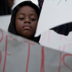 Kevin Etienne holds up a sign as he listens to a news conference condemning President Trump's recent remarks denigrating Haiti, before a march to commemorate the eighth anniversary of the Haitian earthquake, Friday, Jan. 12, 2018, in Miami, Fla.