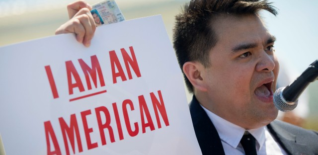 Jose Antonio Vargas, a journalist, filmmaker, and immigration rights activist, from San Francisco, holds up his California Driver's License as he speaks to supporters of fair immigration reform gather in front of the Supreme Court in Washington, Monday, April 18, 2016.