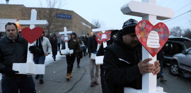 Casildo Cuevas, right, holds a victim's cross as he walks to the Aurora police station after a makeshift memorial Sunday, Feb. 17, 2019, in Aurora, Ill., near Henry Pratt Co. manufacturing company where several were killed on Friday. Authorities say an initial background check five years ago failed to flag an out-of-state felony conviction that would have prevented a man from buying the gun he used in the mass shooting in Aurora. (AP Photo/Nam Y. Huh)