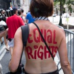 An activist marches in the protest march called the GoTopless Day Parade Sunday, Aug. 23, 2015, in New York. The parade took to the streets to counter critics who are complaining about topless tip-seekers in Times Square. Appearing bare-breasted is legal in New York. But Mayor Bill de Blasio and police Commissioner Bill Bratton say the body-painted women in the square who take photos with tourists are a nuisance.