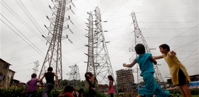 Indian children play near high-voltage electric towers at a slum in Mumbai, India on Thursday, Aug. 2, 2012 photo. India suffered the worst blackouts in history this week, which left over 600 million people without power. The lights are back on, for now, but the crisis is evidence of deep problems in a sector teetering on the edge of bankruptcy for the second time in a decade.
