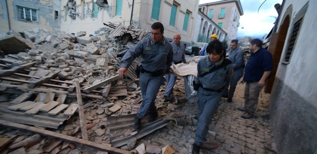 Rescuers carry a victim among damaged buildings after a strong earthquake hit Amatrice, Italy, on Wednesday.
