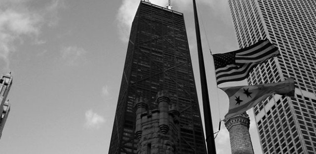 File: American and Chicago flags at half mast.