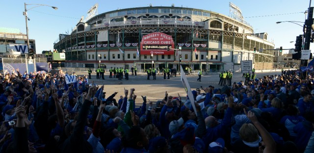 Fans line up outside Wrigley Field for the start of the parade honoring the World Series champion Chicago Cubs baseball team Friday, Nov. 4, 2016, in Chicago. (AP Photo/Paul Beaty)