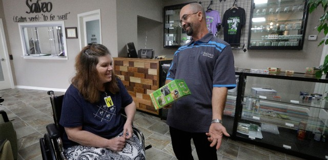 Shamay Flaharty of Lewiston, Ill., who has multiple sclerosis and is hoping cannabis will help ease her pain and headaches, meets with Eric Sweatt, partner and manager of Salveo Health and Wellness, a licensed medical cannabis dispensary, in Canton, Ill, on Oct. 20, 2015. (AP Photo/Seth Perlman)