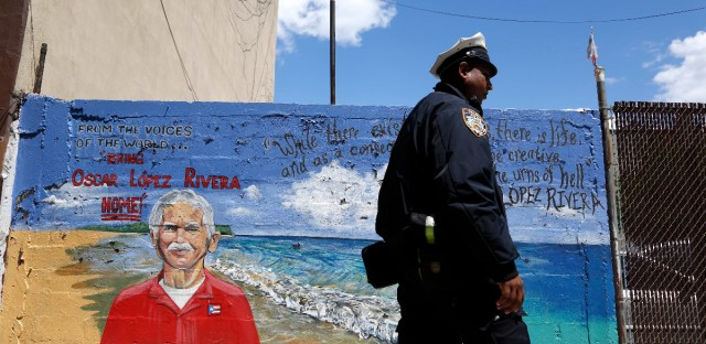 A police officer walks past a mural of Oscar Lopez Rivera in New York on May 9, 2017.