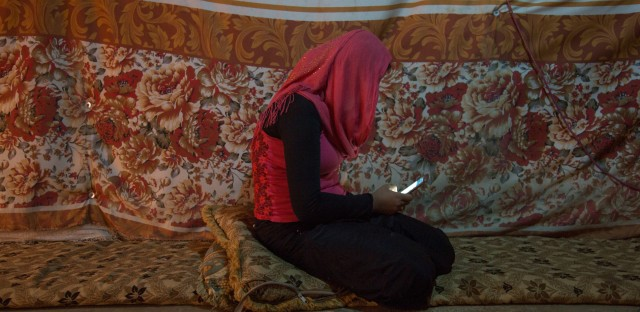 She's a teenager with a cellphone, surfing the Internet. And she's a Syrian refugee who works in the fields up to 14 hours a day. That's the new life of 15-year-old Fatmeh, seen here in the living room area of her family's makeshift shelter.