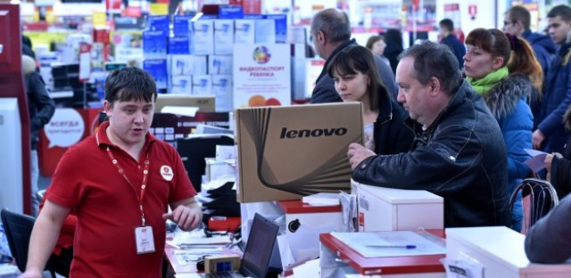 A man holds a laptop in a mall in central Moscow on December 15, 2014. The slumping ruble has unleashed a spending spree as consumers snap up electronics, furniture and cars before prices soar.