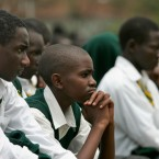 Pupils of the Jamhuri High School in Nairobi listen as then Kenyan President Mwai Kibaki addresses them, Monday, Feb. 11, 2008 as he officially launched free secondary education for all Kenyans.