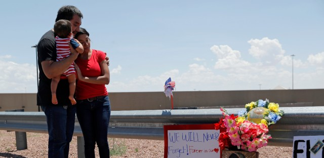 Dr. Julio Novoa, left, and Danielle Novoa, right, visit a makeshift memorial with their 10-month-old son Richard Novoa at the scene of a mass shooting at a shopping complex Sunday, Aug. 4, 2019, in El Paso, Texas.
