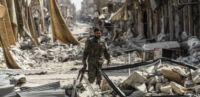 A member of the Syrian Democratic Forces, a group allied with the United States, walks through debris in Raqqa on Monday. The Syrian fighters have retaken most of the city from the Islamic State, one of the group's last strongholds. While ISIS territory is dwindling, finding political solutions to the wars in Syria and neighboring Iraq will remain a major challenge.