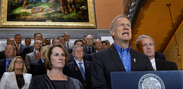 Illinois Gov. Bruce Rauner, surrounded by fellow Republican lawmakers, speaks to reporters outside his office at the state Capitol, Tuesday, May 31, 2016, in Springfield, Ill., as legislators press ahead on the last day of the spring legislative session. Illinois Senate Minority Leader Christine Radogno, R-Lemont, left, and Illinois House Minority Leader Jim Durkin, R-Western Springs, right, look on.