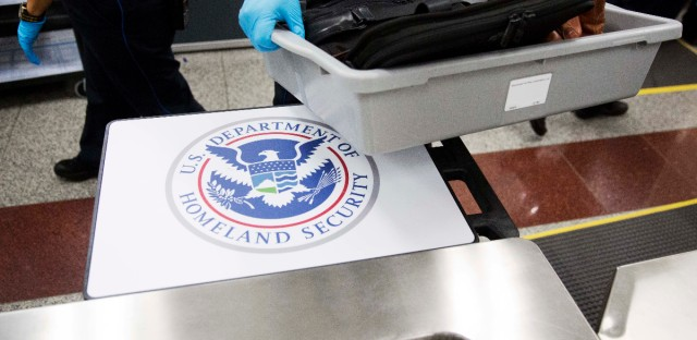 A U.S. Department of Homeland Security seal is seen as a TSA official moves a bin for additional screening at a newly designed passenger screening lane unveiled at Hartsfield-Jackson Atlanta International Airport. The new screening lanes allow multiple passengers to load their belongings onto an automated conveyer belt at the same time. The lanes, the first of its kind in the nation, are aimed at speeding up the security process and are modeled on similar systems at London's Heathrow and Amsterdam's Schiphol airports.