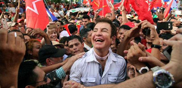 Opposition leader Salvador Nasralla is surrounded by supporters as he arrives for a rally where he reaffirmed his claim on the presidency of Honduras, in the central park of San Pedro Sula, Honduras, Saturday, Jan. 6, 2018.