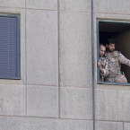 Men in military uniform stand at a window in the Iranian parliament building following an attack on Wednesday in Tehran, Iran. More than a dozen people were killed and many more wounded during twin gun and suicide bomb attacks in Iran's capital.