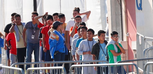 In this March 27, 2019, file photo, Central American migrants wait for food in a pen erected by U.S. Customs and Border Protection to process a surge of migrant families and unaccompanied minors in El Paso, Texas. Late yesterday, hundreds of children were moved out of the U.S. Customs and Border Patrol facility in Clint, Texas, into a shelter system run by the Office of Refugee Resettlement on June 24, 2019.