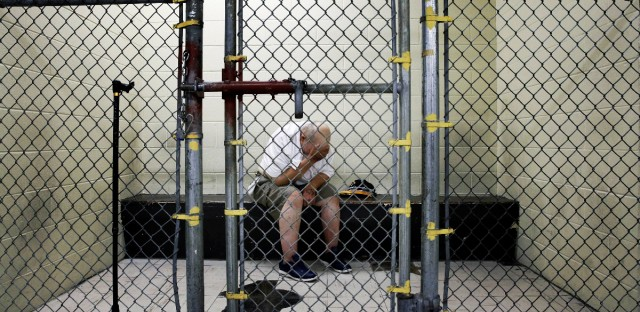 A U.S. veteran with post-traumatic stress sits in a segregated holding pen at the Cook County Jail after he was arrested on a narcotics charge in Chicago.