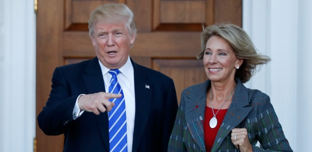 President-elect Donald Trump calls out to the media as he and Betsy DeVos pose for photographs at Trump National Golf Club Bedminster clubhouse in Bedminster, N.J., Saturday, Nov. 19, 2016. (AP Photo/Carolyn Kaster)
