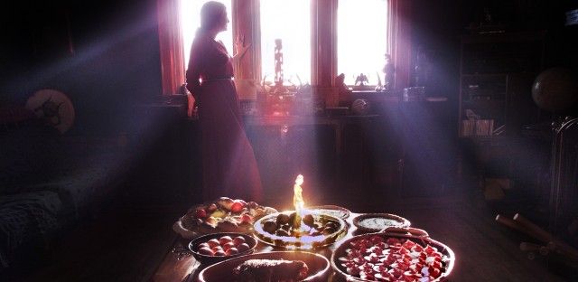 The bounty of the earth is celebrated in the high rituals of pagans. (Above) A Wiccan priestess is silhouetted by the afternoon light. In the foreground are examples of Wiccan cooking for the vernal equinox: (clockwise from near right) beet-pickled eggs; roast beef in tarragon; bowl of eggs boiled with onion skin wrap; bread with eggs; Ukrainian painted eggs; and apple crumble.