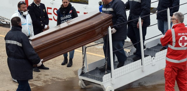 "Men carry a coffin during the arrival of migrants and refugees in the port of Messina following a rescue operation at sea by the Italian Coast Guard ship ""Diciotti"" on March 17 in Sicily. After several quiet weeks, March saw a pick-up in the flow of migrants attempting to reach Italy via Libya, a route through which around 330,000 people have made it to Europe since the start of 2014."