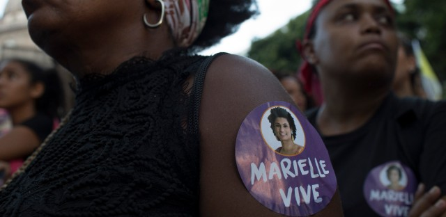 A woman wears a sticker with the photo of councilwoman Marielle Franco during a protest against her murder in Rio de Janeiro, Brazil, Tuesday, March 20, 2018. Franco's murder came just a month after the government put the military in charge of security in Rio, which is experiencing a sharp spike in violence less than two years after hosting the 2016 Summer Olympics.