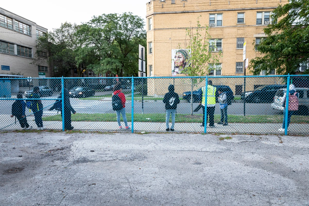 Students wait for the bus in front of Bouchet Elementary Math & Science Academy in Chicago's South Shore neighborhood. More than 74% of students whose neighborhood school is majority black schools are bused to majority black schools.