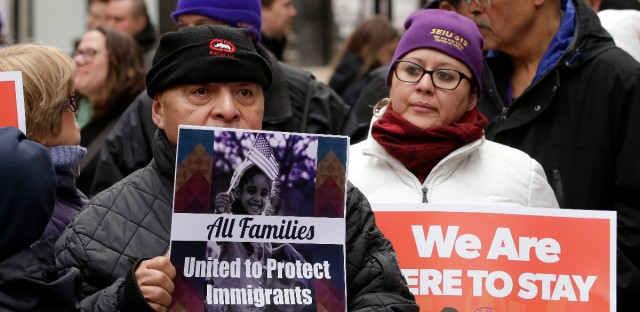 "Wilfredo Mendoza, of Boston, left, and Christina Villafranca, of Malden, Mass., right, displays a placards during a rally called ""We Will Persist,"" Tuesday, Feb. 21, 2017, in Boston. According to organizers the rally was held to send a message to Republicans in Congress and the administration of President Donald Trump that they will continue to press for immigration rights and continued affordable healthcare coverage."