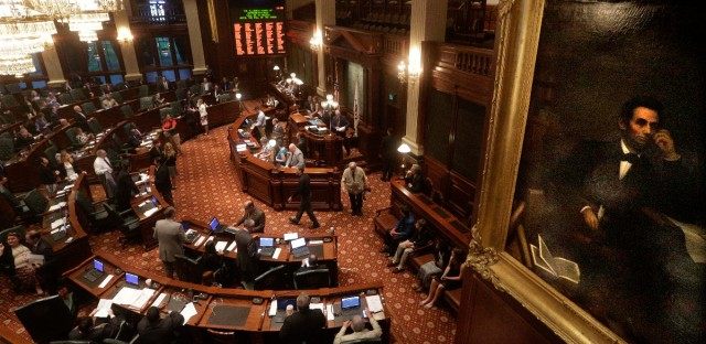 A portrait of Abraham Lincoln overlooks lawmakers as they debate legislation while on the House floor during session at the Illinois State Capitol in Springfield, Ill. in May 2016.