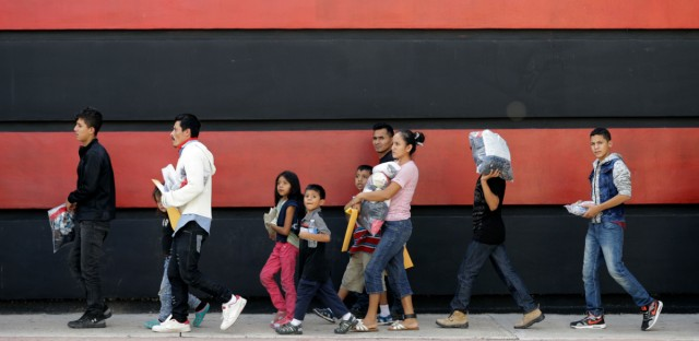 Immigrant families walk along a sidewalk on their way to a respite center after they were processed and released by U.S. Customs and Border Protection, Sunday, June 24, 2018, in McAllen, Texas.