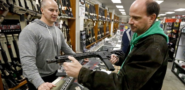 Wes Morosky, left, owner of Duke's Sport Shop helps Ron Detka as he shops for a rifle at his store in New Castle, Pa.
