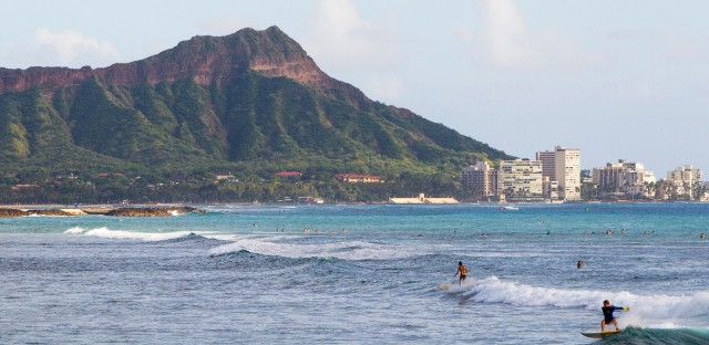Surfers ride waves off Ala Moana Beach Park in Honolulu, with Diamond Head mountain in the background on Nov. 4, 2014.