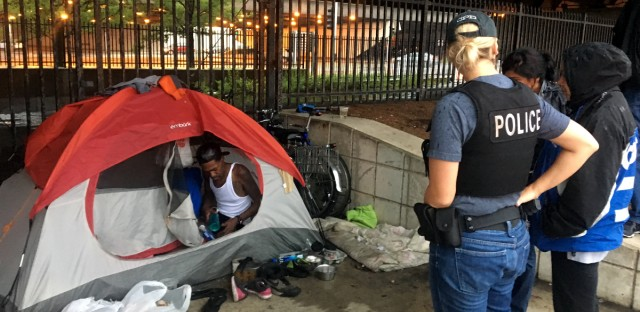 Two Chicago police officers arrived with representatives from the Department of Family and Social Services and Streets and Sanitation Workers to take Smith and Moore's tent on a rainy day in late July. The officers told WBEZ that tents are not allowed in the central business district.