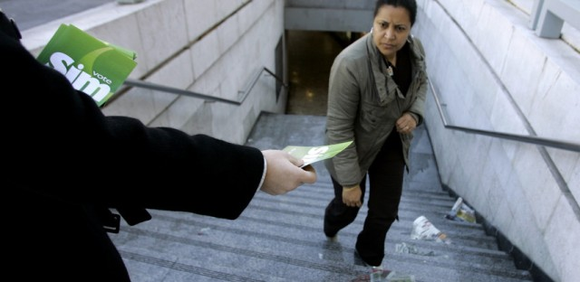 A pro-abortion activist hands out literature in downtown Lisbon.