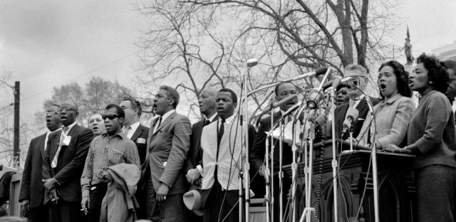 "Civil rights leaders, including Dr. Martin Luther King, Jr., sing ""We Shall Overcome"" at the conclusion of the Selma to Montgomery civil rights march."