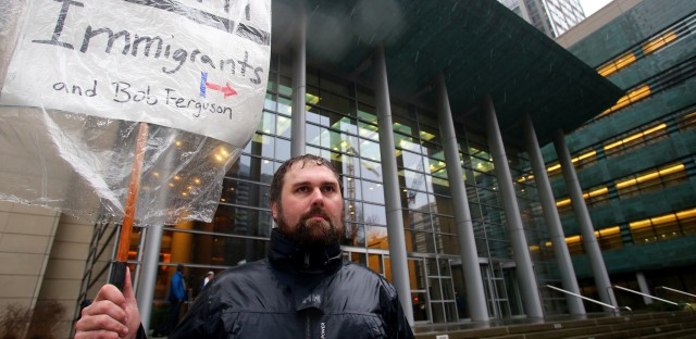 Patrick Wicklund, from Seattle, stands outside the U.S. District Court, Western Washington, on Feb. 3 in Seattle. Washington state Attorney General Bob Ferguson filed a state lawsuit challenging key sections of President Trump's immigration executive order as illegal and unconstitutional.