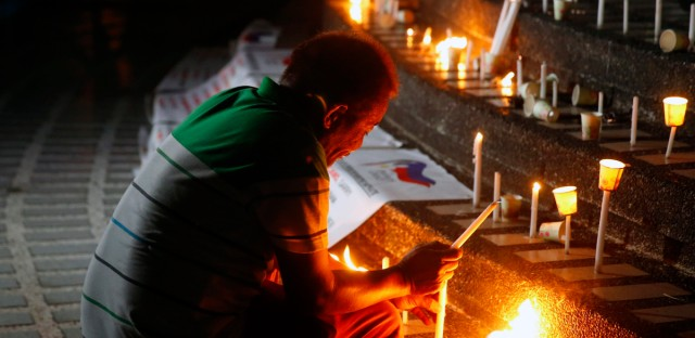 A supporter of opposition senatorial candidates lights candles at the foot of the People Power Monument to pray and urge people to vote on May 13 midterm elections Thursday, May 9, 2019 in Mandaluyong city northeast of Manila, Philippines. Monday's midterm elections which will elect twelve senators, congressmen and local leaders, is largely seen as a test of President Rodrigo Duterte's hold on his leadership.