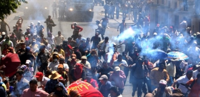 Pro-Zelaya protesters run as police officers fire tear gas at them in the city of Tegucigalpa, Honduras last year.
