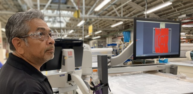 A man wearing plastic glasses stands in front of a manufacturing machine