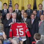President Barack Obama, accompanied by, from left, Chicago Blackhawks head coach Joel Quennville, Blackhawks President and CEO John McDonough and Chairman Rocky Wirtz, holds up a team sweater as he poses for a group photo during a ceremony to honor the 2015 NHL Stanley Cup Champion Chicago Blackhawks, Thursday, Feb. 18, 2016, in the East Room of the White House in Washington.