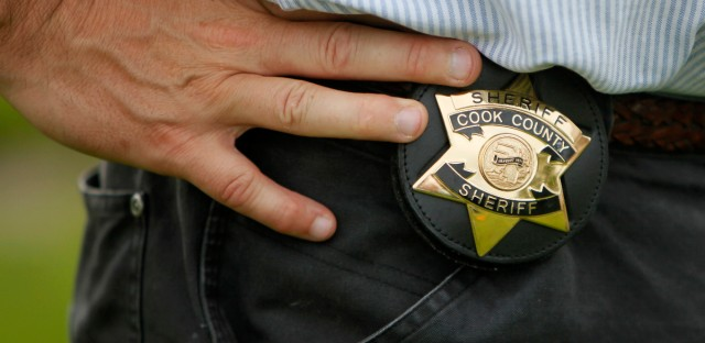 In this photo taken Wednesday, July 15, 2009, the badge of Cook County Sheriff Tom Dart is seen hooked to his belt during his investigation at the Burr Oak Cemetery in Alsip, Ill., where four people were accused of digging up graves and reselling plots in a moneymaking scheme.